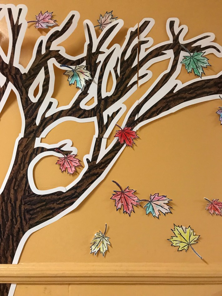 Paper tree with bare leaves and colourful leaves falling. Attached to interior wall.